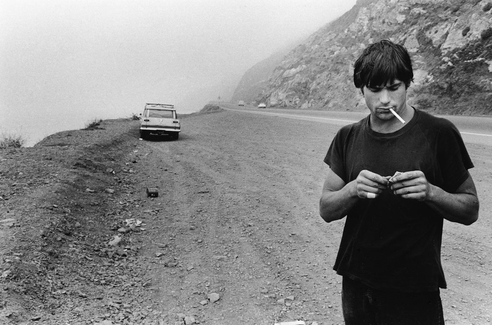 Anthony Friedkin's 1977 photograph 'Clockwork Malibu' shows Rick Dano with a cigarette hanging from his mouth on the side of the Pacific Coast Highway. A new exhibition of Friedkin's work, 'The Surfing Essay,' is on display at Daniel Cooney Fine Art through Dec. 21.