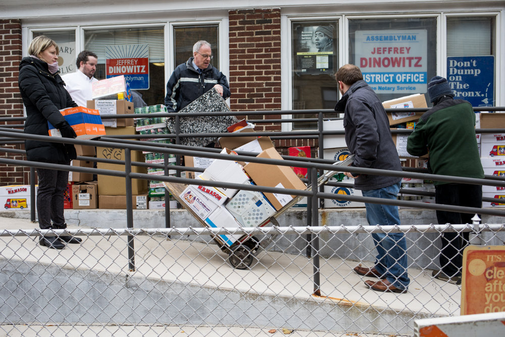 Assemblyman Jeffrey Dinowitz, center, and members of his staff gather and carry boxes of packaged food to several cars as part of its annual holiday canned food drive for Thanksgiving, intended for the Kingsbridge Heights Community Center and the Saint Francis of Rome Food Pantry. A woman police identified as Tamika West, 44, was arrested Dec. 4 after allegedly sneaking into the Assemblyman's Kingsbridge district office through a ground-floor window.