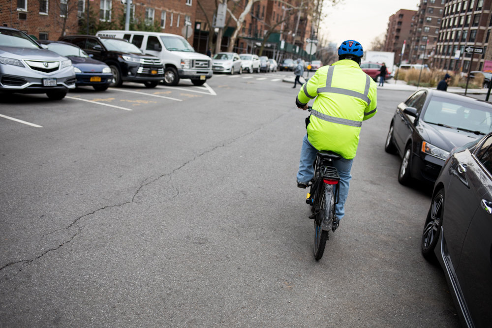 A deliveryman rides an electric bike down Fieldston Road. Councilmen including Ydanis Rodriguez and Fernando Cabrera announced a four-bill package Nov. 28 that would legalize not just so-called e-bikes, but also e-scooters, while also establishing conversion and pilot programs.
