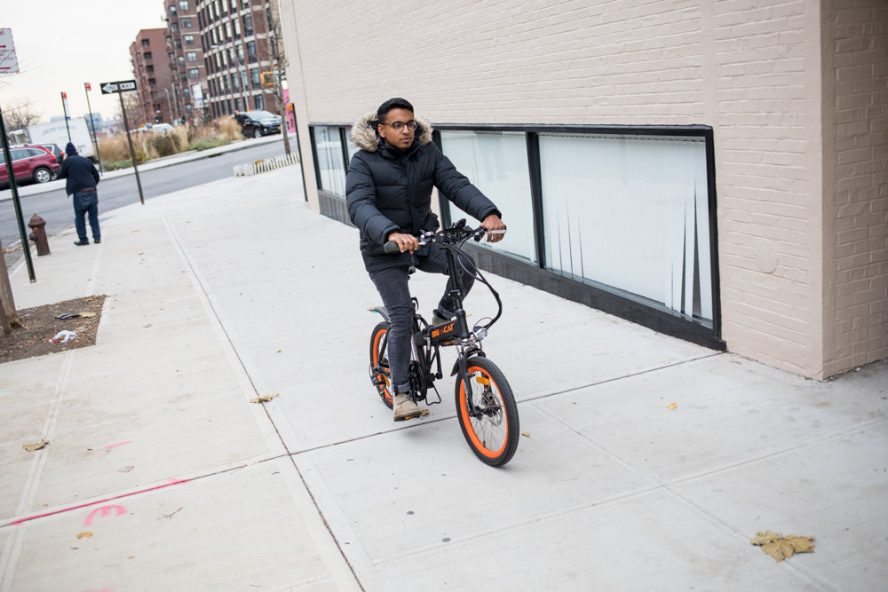 Flemin Reji rides an electric bicycle, something Councilmen Ydanis Rodriguez and Fernando Cabrera hope to legalize, as long as speed is capped at 20 miles an hour. It also would establish a pilot program to test the viability of e-scooters — capped at 15 miles an hour — along the L train corridor, due to be shut down next year.