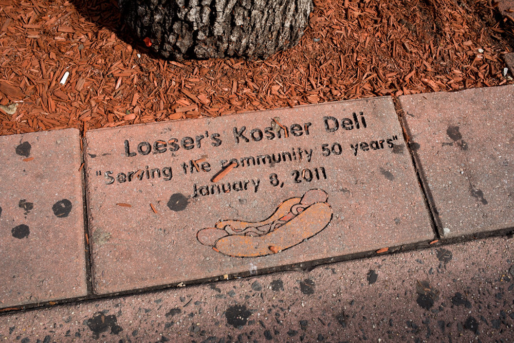 A ceremonial brick from 2011 commemorates the 50th anniversary of Loeser's Kosher Deli, a staple of West 231st near Broadway. The family behind the deli is pushing to have West 231st Street named in the eatery's honor, but faces a major obstacle: Community Board 8's guidelines on street renaming only honor people who have died.