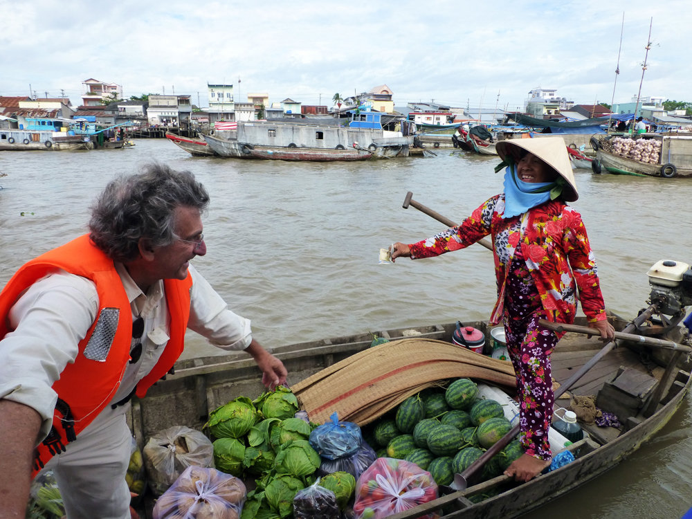 Riverdale resident Bill Caplan purchases a melon at the Cai Rang floating market in the Mekong Delta of Vietnam.
