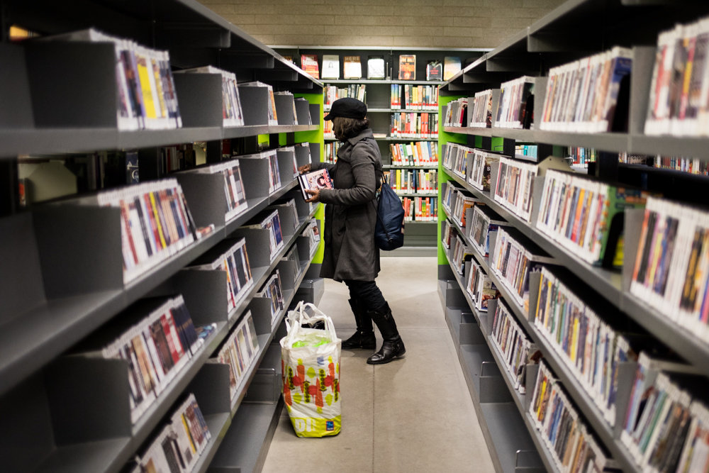 A patron browses the DVD section on the main floor of the Kingsbridge Library, which is designated as a hub by the New York Public Library. The Kingsbridge location will absorb the DVD collections from nearby libraries, which will expand its offerings.