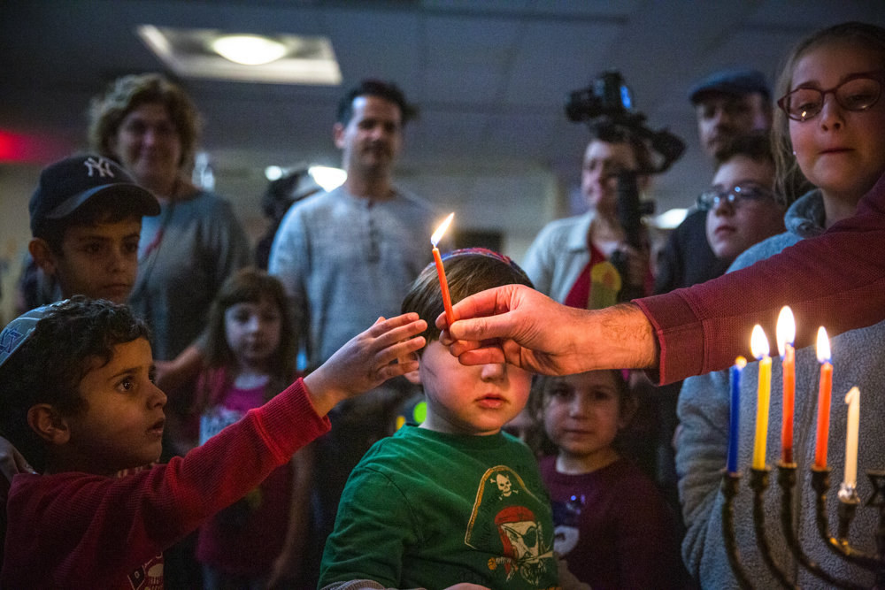 Jay Gindin gives Shai Maudi, 5, a candle to light the Hanukkah menorah as celebrants sing a prayer. The Congregation Beth Aharon at the Hebrew Institute of Riverdale recently celebrated its 20th anniversary.