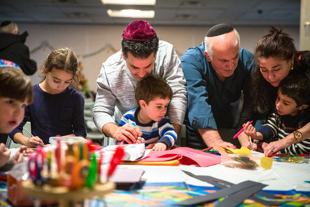Avihai Vissor, center, helps son Yair color a paper dreidel at a Hanukkah celebration held by Congregation Beth Aharon at the Hebrew Institute of Riverdale. The Sephardic congregation recently celebrated its 20th anniversary.