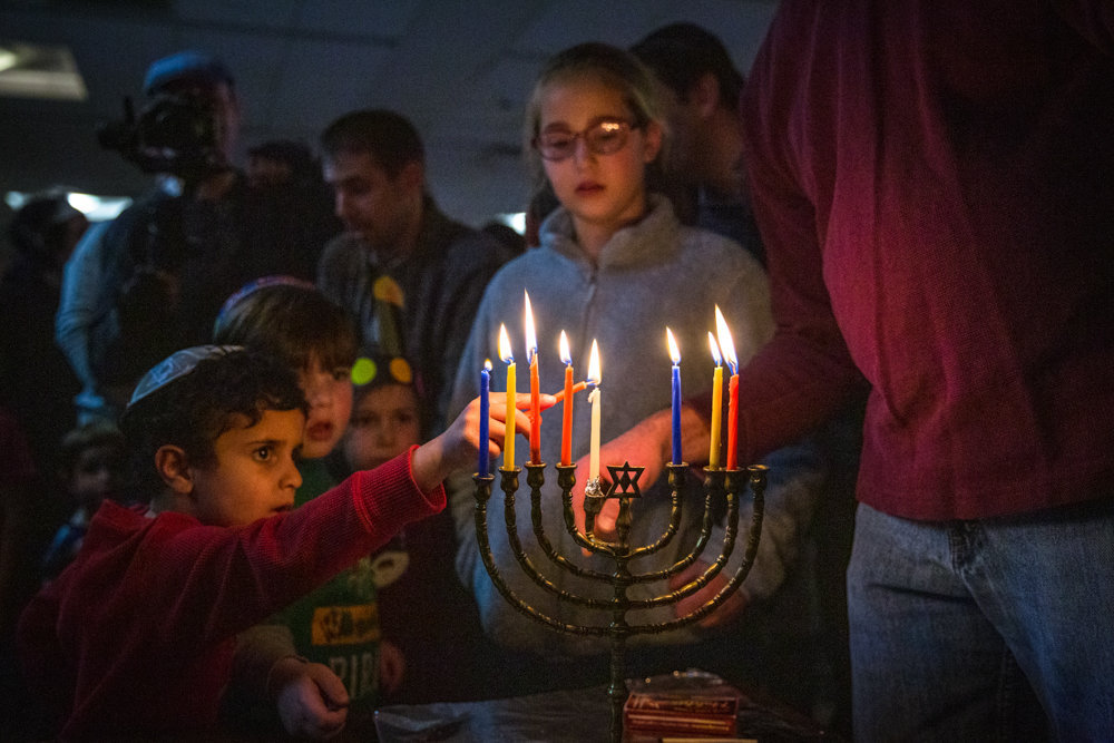 Shai Maudi lights a candle on the menorah while people sing a prayer at Congregation Beth Aharon's Hanukkah celebration at the Hebrew Institute of Riverdale. The two congregations have shared the space — albeit not at the same time — for the past 20 years.