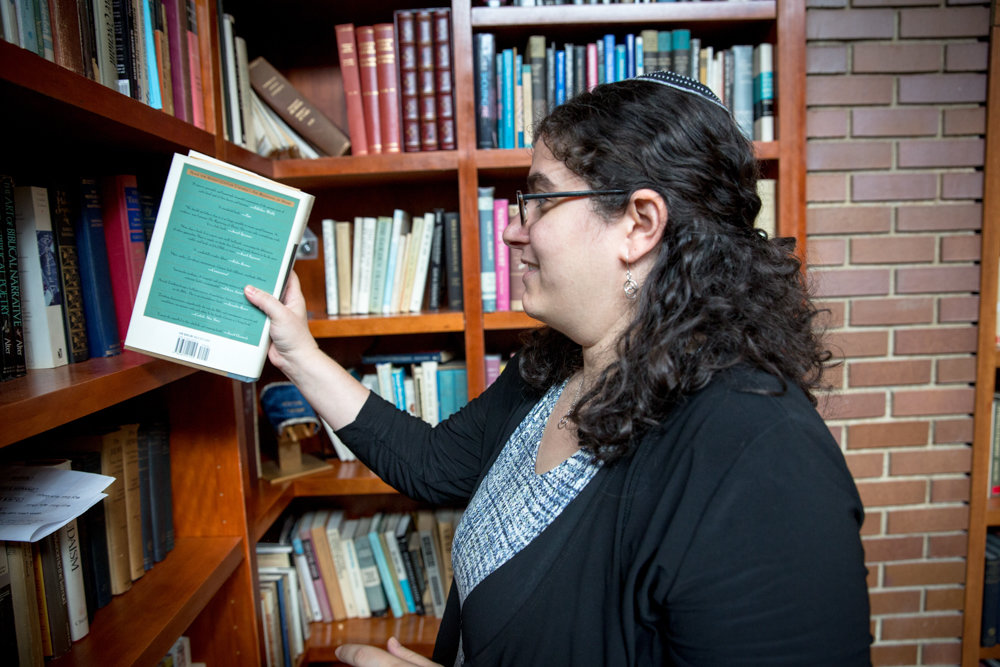 Rabbi Katie Greenberg takes a book off the shelf at the Conservative Synagogue Adath Israel of Riverdale. Greenberg is the synagogue's new engagement and programming director, which means she helps bridge the gap between the community and the congregation.