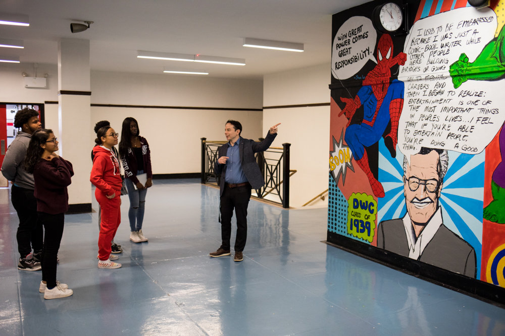 Pierre Orbe, the principal of DeWitt Clinton High School, talks with students about Stan Lee's influence on him and late comic book legend's legacy at the school in front of a mural painted by Delania Alma. Lee graduated from Clinton in 1939, and died last November at 95.