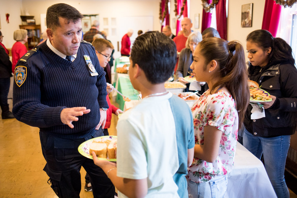 Capt. Emilio Melendez speaks in Spanish with children at a Christmas party at the St. John-Visitation Parish Pastoral Center. Melendez took over the 50th Precinct's top job, succeeding Deputy Inspector Terence O'Toole. Melendez, a 30-year veteran of the police department, was expected to begin has plans to tweak things in the 5-0 at the beginning of the year.