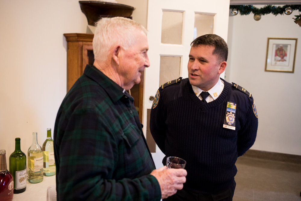 Capt. Emilio Melendez speaks with Ed Byrne at a Christmas party at the St. John-Visitation Parish Pastoral Center. A 30-year veteran of the police department, Melendez succeeded Deputy Inspector Terence O'Toole.