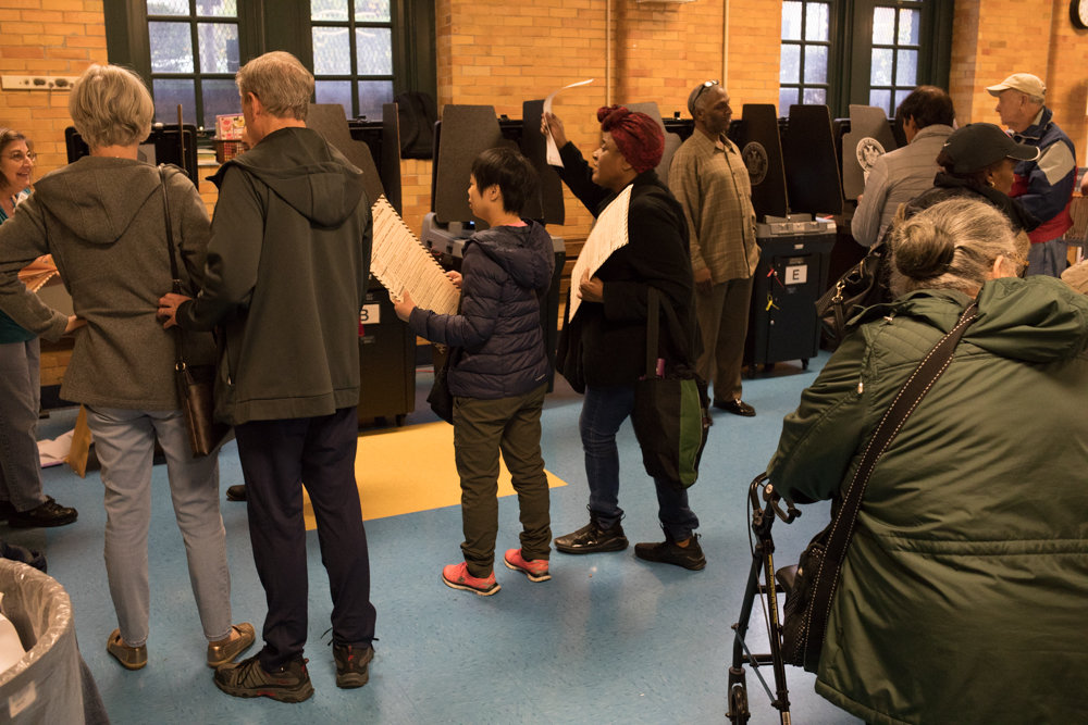 A crowd of people waits to scan their completed ballots at P.S. 81 on Nov. 6. Election Day in New York City was marked by faulty ballot scanners, which compounded the inherent difficulty in voting throughout state. Making voting easier is one of Gov. Andrew Cuomo's New Year's resolutions.