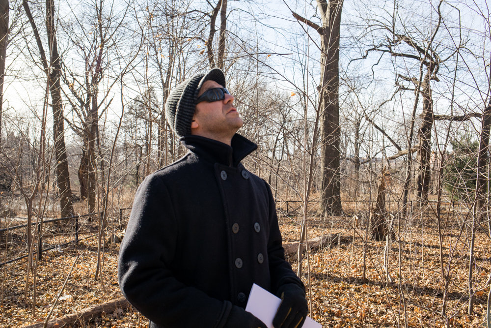 Kingsbridge Historical Society president Nick Dembowski looks up at the trees surrounding a colonial-era gravesite in Van Cortlandt Park. The gravesite is a short walk from a spot where skeletons were unearthed in the early 20th century along the Putnam Trail believed to have belonged to African-American slaves.