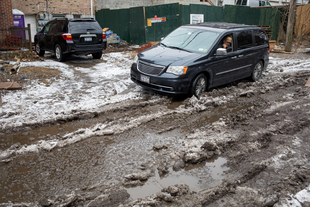 Harry Martinez considers whether or not he will try driving through a deep, slushy puddle on Old Albany Post Road in order to get to West 251st Street. Martinez ultimately decided not to drive through. The road, which is owned by the state, has been in disrepair for years.