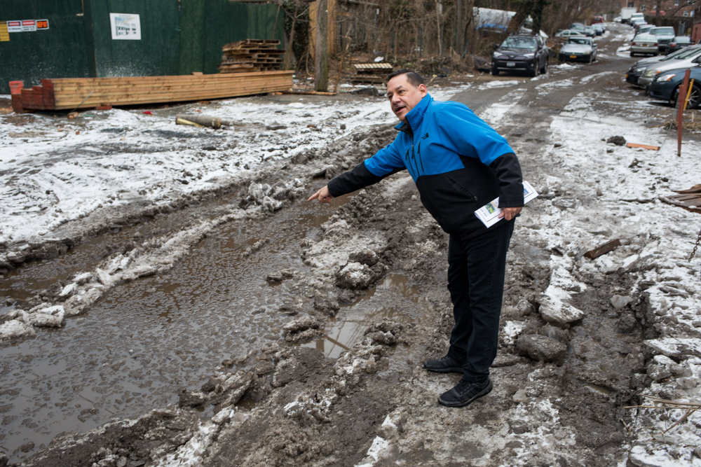 Luis Malavé indicates the location of a ConEd gas line beneath a slushy puddle on Old Albany Post Road. Malavé resides on Post Road, with the back of his home facing the dilapidated state-owned street. Local elected officials are calling for the city to purchase the strip of land to properly maintain it.