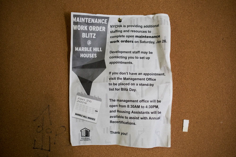 A sign detailing the New York City Housing Authority's increased staffing to take care of open maintenance work orders is pinned to a bulletin board inside 49 W. 225th St., one building among the sprawling Marble Hill Houses. Some residents suffered heat and hot water failures during a brutal cold spell Jan. 21.