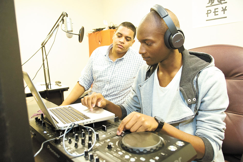 Erick Jhon Peguero, left, looks on as Poche Wilson makes adjustments during a broadcast of a program they hosted together on Lehman College's student-run radio station in 2016. Unlike Lehman, some pirate radio operators broadcast illegally, flouting FCC regulations. Some of these so-called pirate radio signals have even been detected around Spuyten Duyvil as recently as last November.