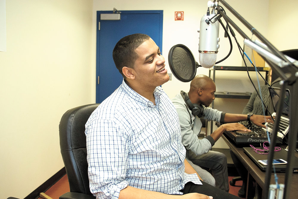 Erick Jhon Peguero, left, speaks into the microphone during a broadcast of a program he co-hosted with Poche Wilson, right, on Lehman College's radio station in 2016. Some pirate broadcasters, however, take to decidedly underground means of reaching various audiences beyond legitimate radio's so-called mainstream audience.