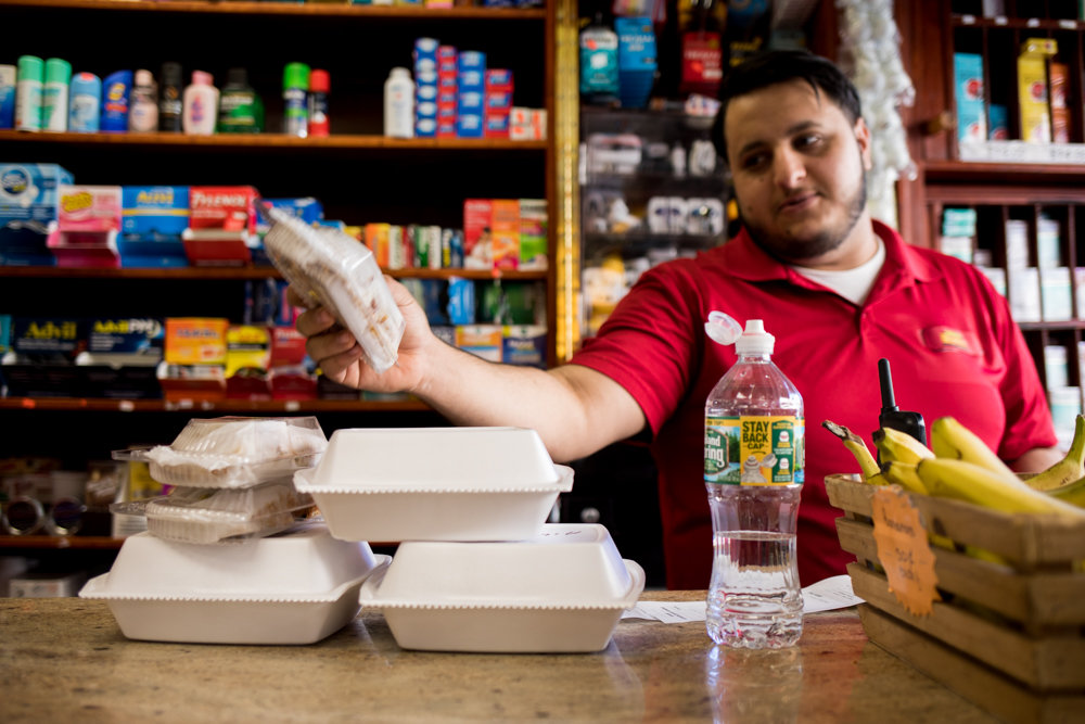 Moe Aly, an employee of New Riverdale Gourmet Deli on West 238th Street, bags an order of food for a customer. Aly knows that plastic foam containers have been a mainstay of grub spots like his, but doesn't think the city's ban on foam — which took effect Jan. 1 — will have much of an effect on business.