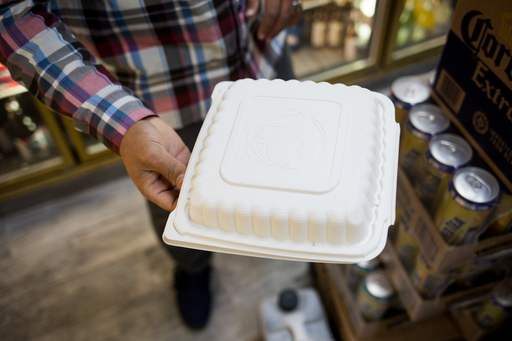 Jay Aowas, owner of Jasper's Deli on West 238th Street, holds out a plastic food container. Aowas made the switch from plastic foam to a different kind of plastic some six months ago, ahead of the city's foam ban Jan. 1. He figured the fines weren't worth it, and wanted to get a head start transitioning to alternative food packaging, including the plastic-based containers he uses now. While they cost a bit more, Aowas believes eliminating foam is better for the environment.