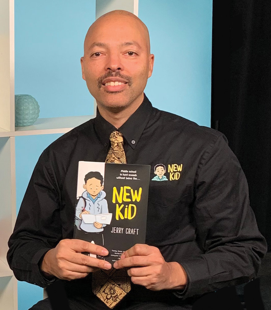 Jerry Craft smiles with a copy of his soon-to-be-published graphic novel, 'New Kid,' which details the story of an African-American student finding himself as the new kid at an affluent, mostly white school. It's based on Craft's experience as a student at Ethical Culture Fieldston School.