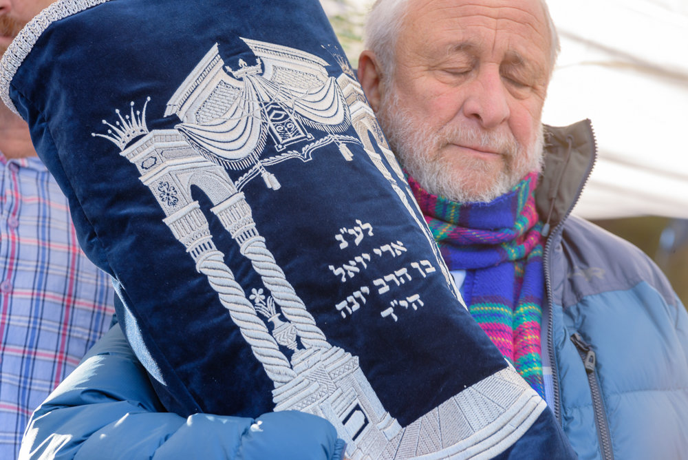 Rabbi Yonah Fuld holds a Torah dedicated to the memory of his son Ari, who died in Israel last September at 45. The Torah was donated anonymously to SAR Academy where Ari went to his school and where is father once served as principal.