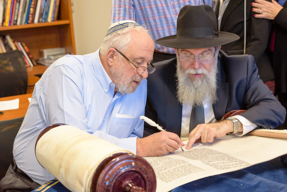 Rabbi Yonah Fuld, left, inscribes a Torah with the help of a sofer, Rabbi Heshy Pincus, at SAR Academy. The Torah was donated anonymously to the school in honor of Fuld's son Ari, an SAR alum who died in Israel last September.