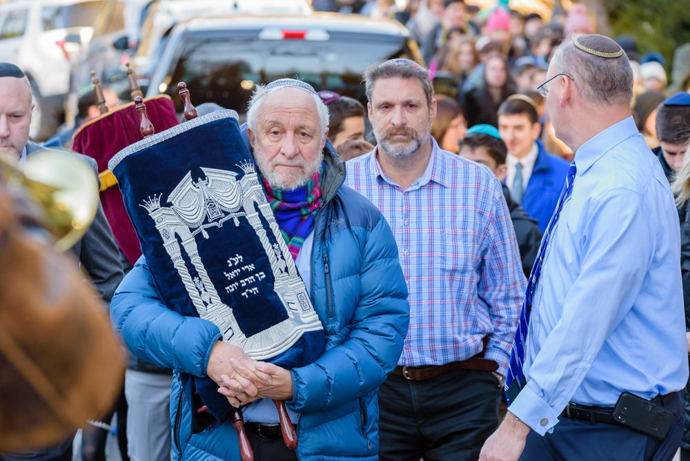 Rabbi Yonah Fuld, center, walks with a Torah dedicated to the memory of his late son Ari. The Torah was donated anonymously to SAR Academy where Ari went to school and where his father was once the principal.