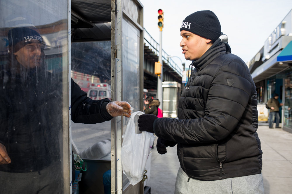 Jeremy Serrano picks up his order from Rachid Tahzima, who runs the Halal Brother food cart on Broadway just south of West 231st Street. Tahzima — who says he already diligently cleans his mobile food establishment — believes it's a good idea food carts receive letter grades from the city's health department so customers can know the quality of service and cleanliness they're getting. Health inspectors started grading mobile vendors in January.