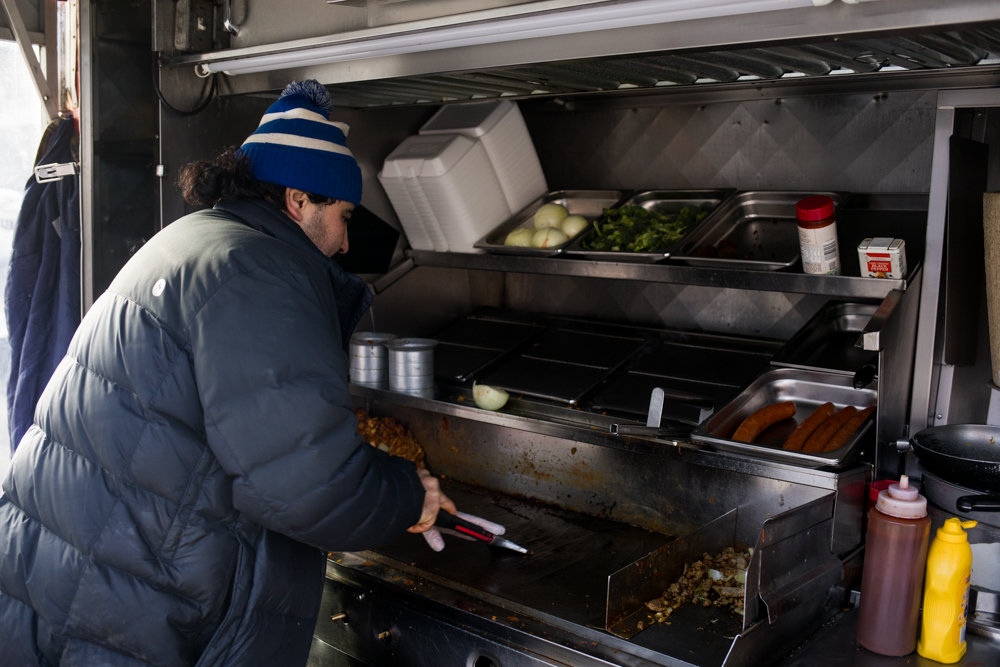 Rachid Tahzima cleans the grill in his food cart, Halal Brother, on Broadway just south of West 231st Street below the elevated 1 train tracks. A well-loved purveyor of gyros, hot dogs and more, Tahzima is in favor of the city health department's effort to assign letter grades to food carts based on criteria like freshness of ingredients and how clean and organized the space and equipment are maintained.