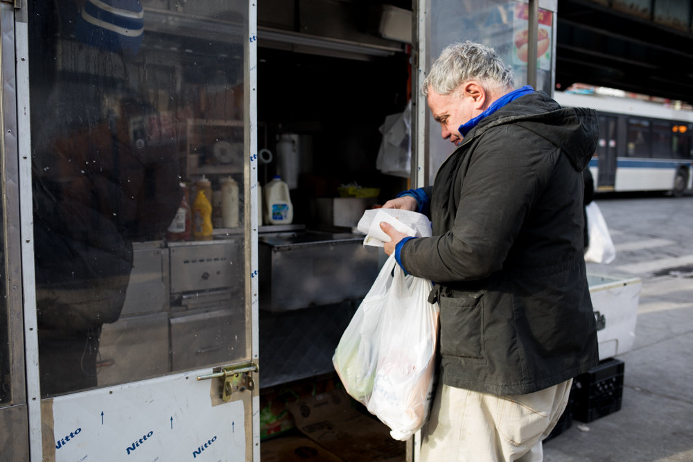 A customer waits for his second hot dog from the Halal Brother food cart on Broadway just south of West 231st Street. The city's health department is now grading food carts based on cleanliness, organization, freshness of ingredients — as it has restaurants for years. While Rachid Tahzima, who runs the cart, has yet to receive his grade, he's aiming for an A, keeping his cart pristine.