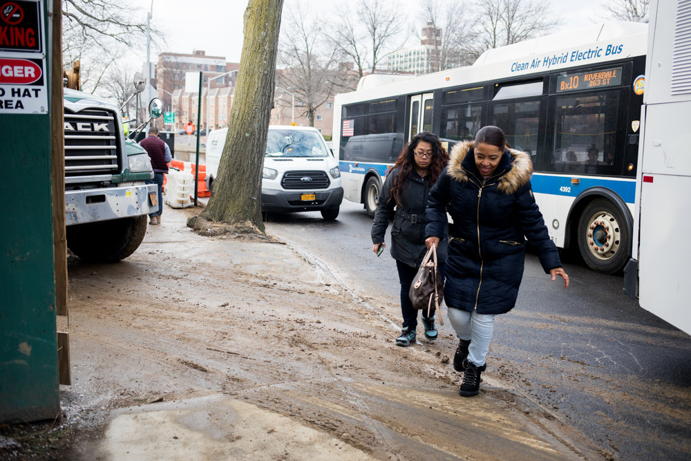 Commuters walk toward the sidewalk after disembarking from a northbound Bx10 bus at 3128 Henry Hudson Parkway where ongoing construction has narrowed the road.
