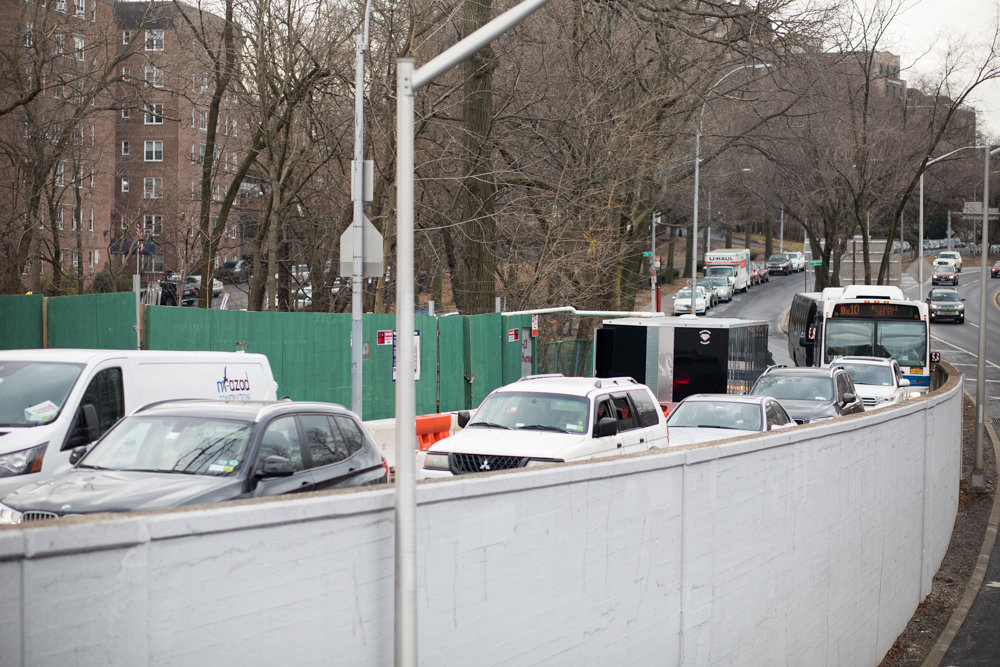 A line of cars and a Bx10 bus slowly drive past ongoing construction at 3128 Henry Hudson Parkway where a construction barrier has narrowed available road space.