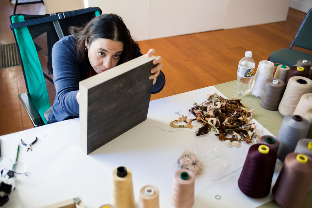 Melissa Calderón embroiders a piece of wood as part of her artistic practice in the Winter Workspace program at Wave Hill. Calderón seeks to merge her love of embroidering with wood, an unconventional material.