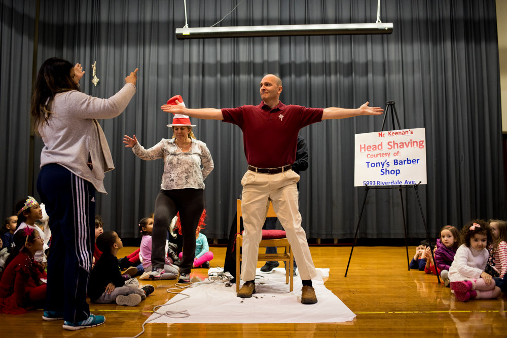 St. Margaret of Cortona School principal Hugh Keenan stands triumphantly after having his head shaved at the start of an assembly Feb. 1. Keenan's newly bald pate came after his students read more than 20,000 minutes worth of books, and raised some $10,000 in the process.