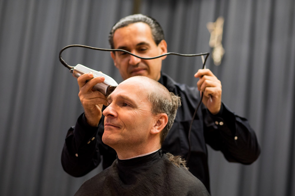 Tony Dulaj shaves the hair off the head of St. Margaret of Cortona School principal Hugh Keenan. The administrator offered the follicular spectacle as a reward for his students reading more than 20,000 minutes worth of books, while raising some $10,000.