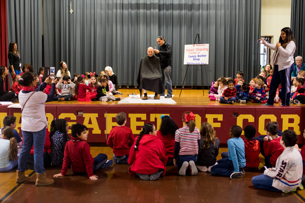 Students and faculty watch as principal Hugh Keenan gets his hair shaved off at the St. Margaret of Cortona School. The trip to the barber was thanks to his students reading more than 20,000 minutes worth of books.