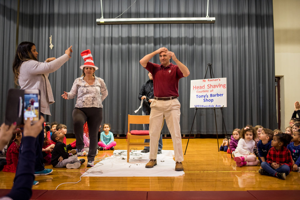 St. Margaret of Cortona School principal Hugh Keenan feels his newly bald head as students and faculty look on. He took the hairless plunge after St. Margaret students surpassed Keenan's goal of reading 20,000 minutes worth of books.