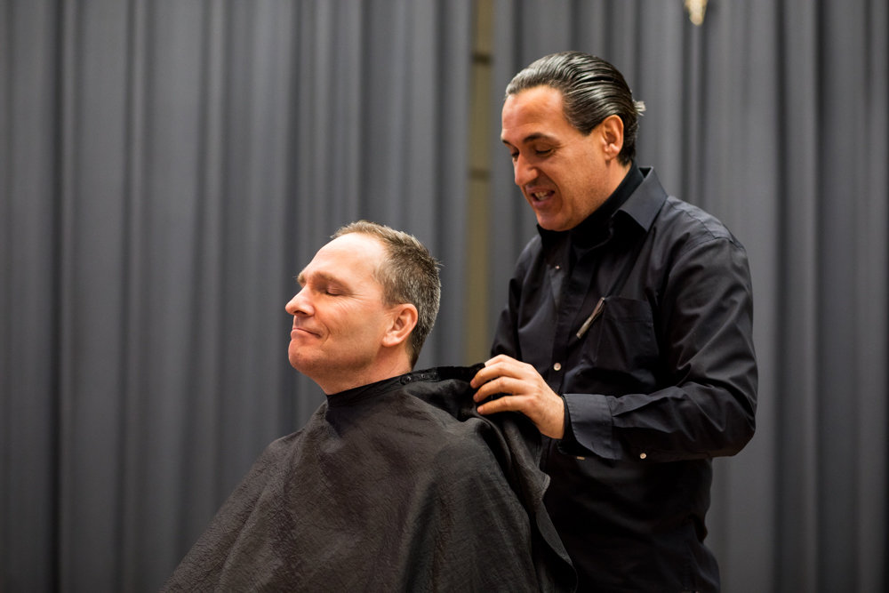 St. Margaret of Cortona School principal Hugh Keenan steels himself before getting his hair shaved off by Tony Dulaj, right, owner of Tony's Barber Shop on Riverdale Avenue.