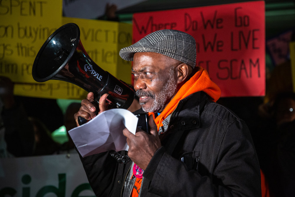 Fitzroy Christian, a leader of Community Action for Safe Apartments, chants into a megaphone at a rally ahead of a rent control-focused town hall last week in Mount Eden.