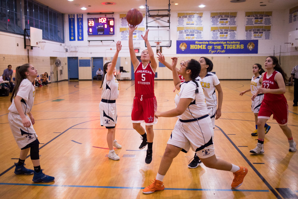 American Studies' Suzuki Lin splits a trio of Riverdale/Kingsbridge Academy defenders for two of her 10 points in the Senators victory over the Lady Tigers in the regular-season finale for both teams.