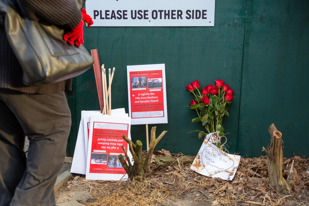 At the end of a vigil in support of the Villa Rosa Bonheur, signs and roses rest against a construction barrier in front of the historic apartment building.
