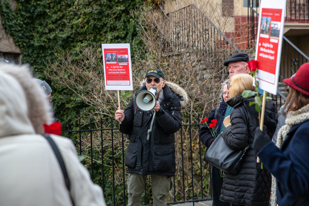 Perry Brass, center, talks about the history of the Villa Rosa Bonheur's sister buildings, the Villa Charlotte Brontë and the Villa Victoria, at a vigil in support of the Villa Rosa Bonheur, a historic apartment building located at 2395 Palisade Ave.