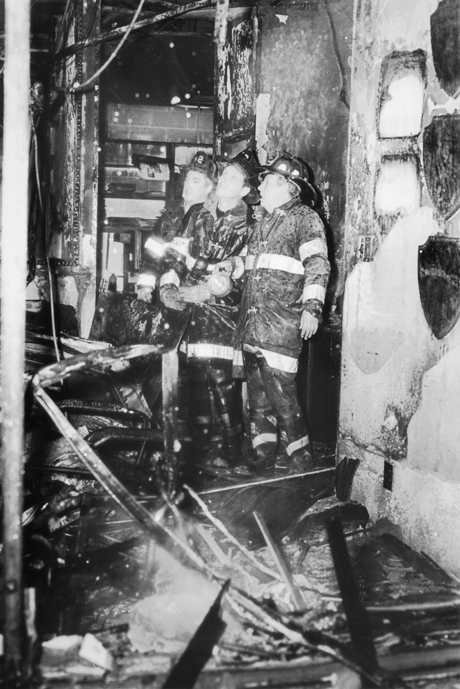 Firefighters analyze the damage inside the Broadway office of The Riverdale Press following the Feb. 28, 1989, firebombing.