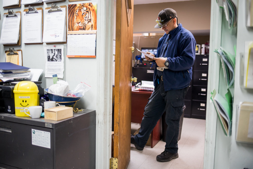 Angel Ortega, who supervises maintenance at Briar Oaks apartments in Riverdale, peruses a document in his office. Before Briar Oaks, Ortega worked in low-income housing. His union, 32BJ SEIU, seeks fair wage increases for the borough's 3,000 residential workers before their current contract expires March 14.