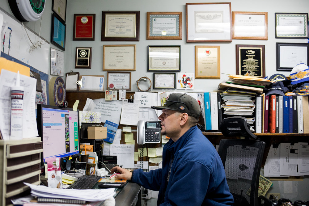 Angel Ortega checks email in his office at Briar Oaks apartments in Riverdale. The longtime superintendent has overseen maintenance of the Henry Hudson Parkway property for more than a decade. As the Bronx's cost of living has increased, Ortega's union is seeking wage increases for residential building workers.