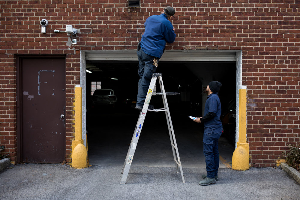 Angel Ortega — who oversees upkeep of Riverdale's Briar Oaks apartments — replaces a lamp above a parking garage entrance with help from porter Luis Santos. Their union, 32BJ SEIU, looks to maintain health and pension benefits for the Bronx's 3,000 residential workers ahead of when their contract expires March 14.