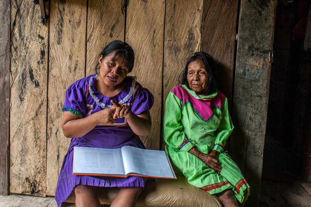 María Noelia Queraguema Nacavera, a midwife apprentice, left, educates Embera women on the elimination of female genital mutilation at the Reserve of Santa Marta in Risaralda, Colombia, in 2004. Her mother — and the eldest midwife of the indigenous reserve, Feliciana — sits next to her.