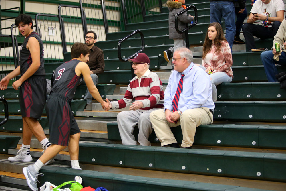 Al Davis, center, shakes hands with Jake Klores during the Buzzell Games in 2016. Davis worked as a coach at Riverdale Country School. He died Feb. 6 at 94.