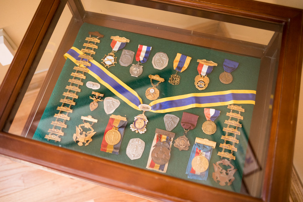 A collection of medals sit in a glass case inside the Fieldston headquarters for the Old Guard of the City of New York, a veterans' organization dating back to the early 1800s dedicated to preserving New York's military history.
