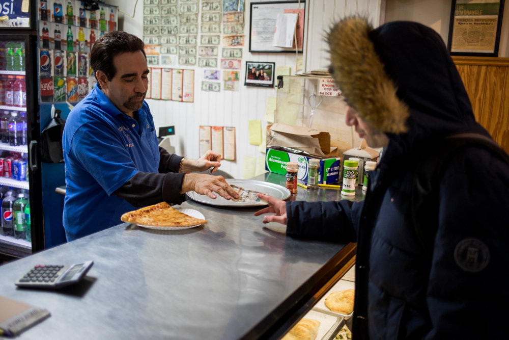 Louis Porco takes a customer's payment at Broadway Joe's, the pizza joint he took over from his father. For Porco, consistency is key, and he sees no reason to mess with the formula that has kept his establishment in business for a half-century.